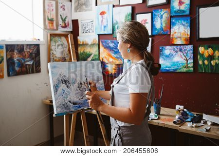 Portrait of young beautiful middle age white Caucasian woman artist drawing painting in art studio with acrylic paints on canvas. View from back. Lifestyle activity hobby concept