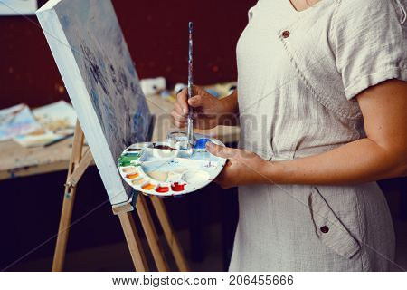 Closeup of young middle age white Caucasian woman artist drawing painting with acrylic paints on canvas. Female hands holding paintbrushes and palette in art studio. Lifestyle activity hobby concept