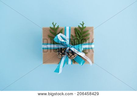 Gift Box Wrapped Of Craft Paper, Blue And White Ribbons And Decorated Fir Branches And Pinecones On