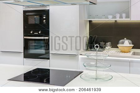 Modern kitchen furniture with contemporary kitchenware like hood black induction stove faucet sink and built-in oven in house.