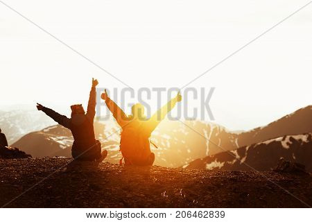 Happy couple or two friends having fun at sunset time on mountain's top. Space for text