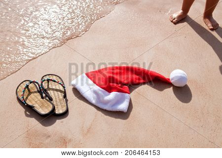 Santa's hat and women's slap on the shore of the Red Sea. Baby naked legs on the sand. Celebrating the new year at the resort