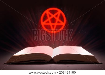 An open book with rays and a pentagram in levitation. The Book of the Devil or Satan. 3D rendering