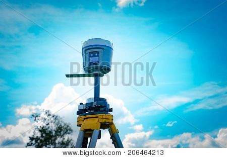 GPS surveying instrument on blue sky background