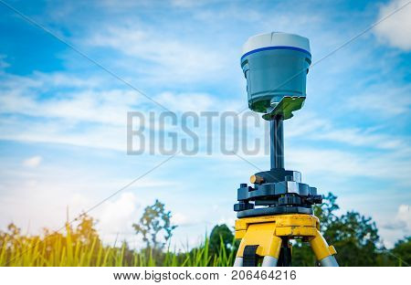 GPS surveying instrument on blue sky and rice field background