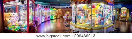 BANGKOK THAILAND - AUGUST 11: Various kinds of crane crabber arcade machines light and lined up in an arcade in Central shopping mall on August 11 2017 in Bangkok.