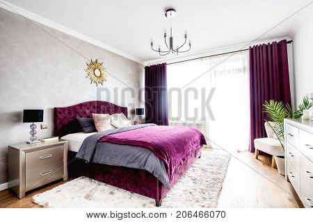 Simple And Stylish Bedroom Interior With Double Bed, Purple Bedding And Modern Nightstands