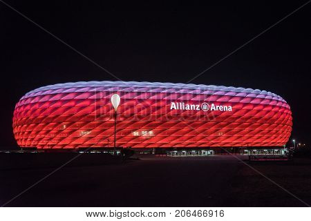 MUNICH GERMANY - 26 SEPTEMBER 2017: Allianz Arena the football stadium of FC Bayern illuminated in red with white on the top at night
