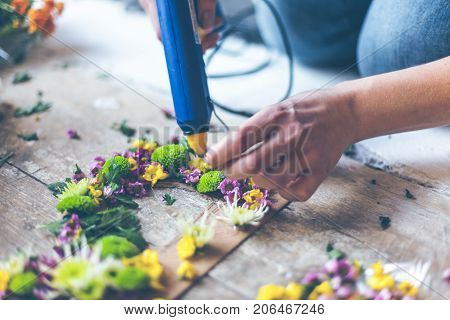 Florist making flower decoration with letters and glue. Indoors natural light shot with small depth of field
