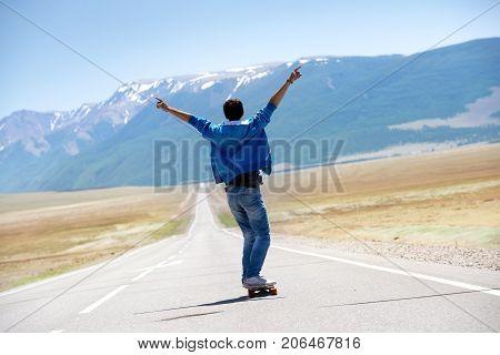 Man skating or longboarding at long straight road at mountain range in winner pose