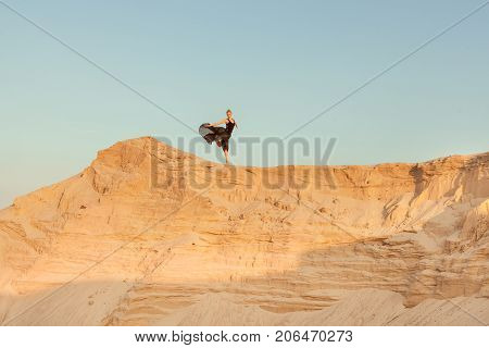 Woman runs down the of a sand dune she is high against the sky.
