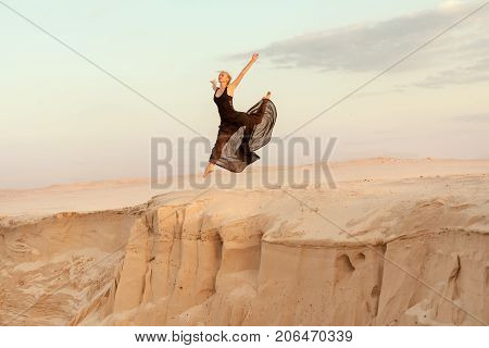 Woman while dancing jumped into the abyss with the dune sand.