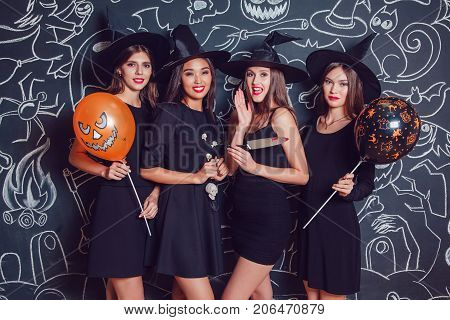 Beautiful girls in suits of witches blow up confetti on a dark background with a picture. Halloween.