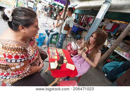 BANGKOK THAILAND - DECEMBER 22 2007 : The Chatuchak Weekend Market is the largest market in Thailand. a fortune teller reads in tarot cards
