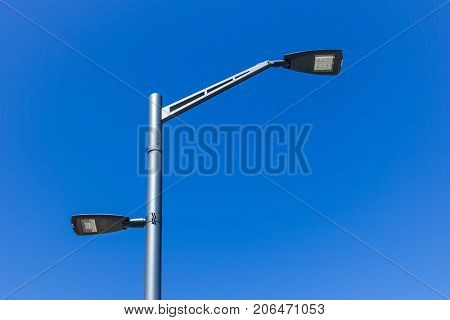 Double street light lamp post or lantern on a blue sky background
