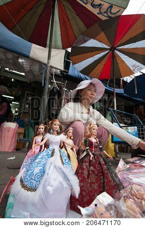 BANGKOK THAILAND - DECEMBER 22 2007 : The Chatuchak Weekend Market is the largest market in Thailand. A woman selling fashion dolls