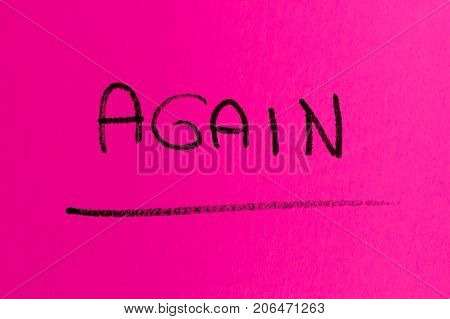 AGAIN word made with spray paint on pink background