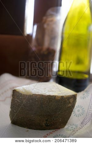 wedge of sardinian pecorinowith in background a bottle of red wine