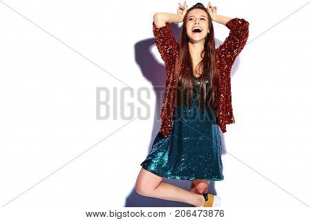 Beautiful caucasian smiling hipster brunette woman model in bright shinny reflecting summer stylish jacket and green dress isolated on white background. Making bunny ears