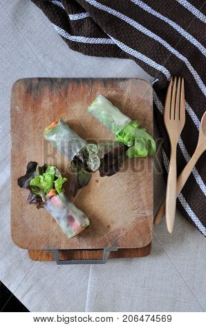 Fresh veggies rolls on wooden cutting board with wooden fork