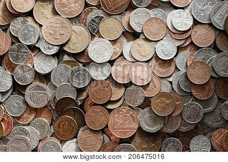 Low denomination British currency. Background image of mixed coins in a pile with selective focus.