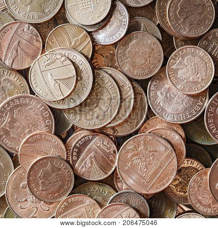 Low denomination British currency. Background image of one and two coins in a pile.