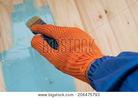 worker paints board blue paint. the employee paints the a wooden table. worker paints wooden board. brush in hand. hand in gloves. House renovation