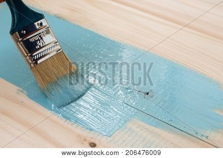 worker paints board. the employee paints the a wooden table. worker paints wooden board. blue paint