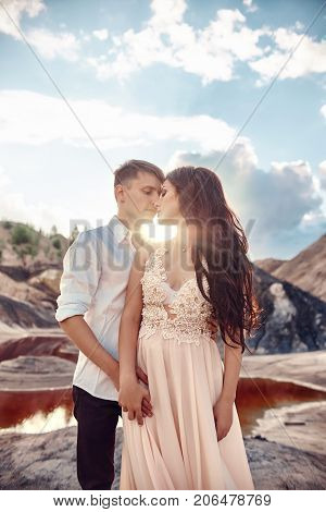 Sexy Couple In Love Kissing And Hugging On The Backdrop Of Fabulous Mountains. Red Blood Lake. A Wom