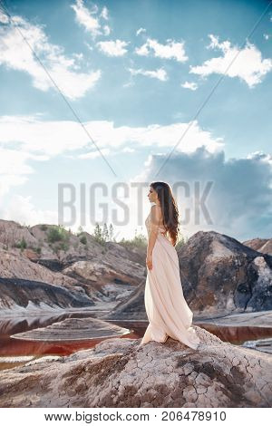Sexy Brunette Woman In Long Dress Standing In The Wind On A Background Of Mountains And Red Lake. Wi