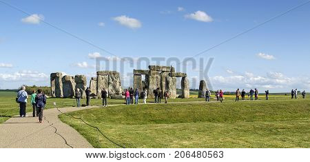 Amesbury, Wiltshire, UK: May 12, 2015: Stonehenge is a prehistoric monument in Wiltshire, England it consists of a series of standing stones. Tourists wander around the site.
