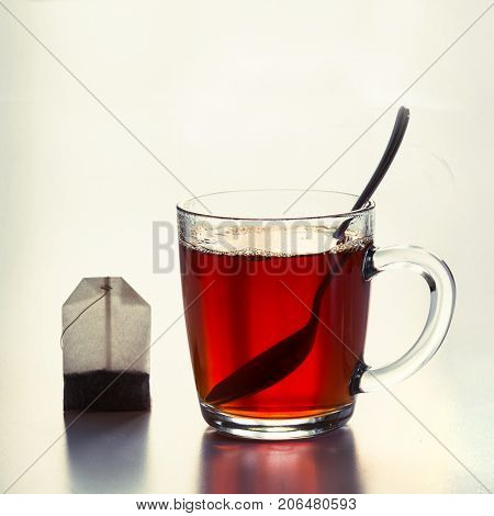 Glass cup of hot black tea and teabag on white. Side view. Close up.