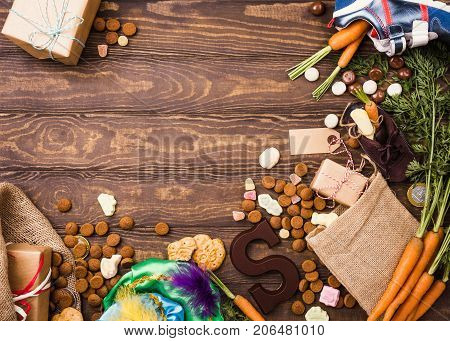 Dutch holiday Sinterklaas background with gifts, pepernoten, chocolate letter, sweets and childrens shoe with carrots for Santa's horse. Flat lay with copy space.