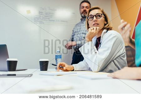 Team of medical professionals discussing during the meeting in boardroom. Woman doctor in staff meeting at hospital.