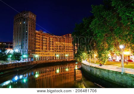 Bilbao, Spain. City downtown with a Nevion River and historical buildings in Bilbao, Spain at night. Blue dark sky