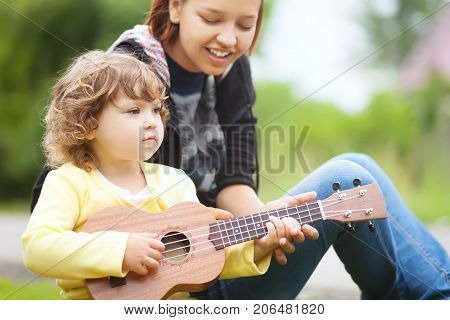 Young attractive nanny teachs little girl playing ukulele sunny day outdoors. Early music education. babysitting. elder sister. young mother