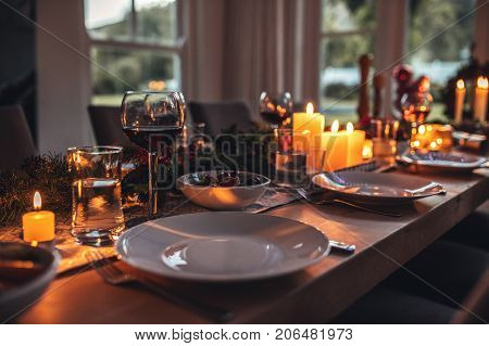 Close up shot of christmas festive table with no people. Dining table with plates wine glasses and candles.