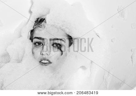 Closeup view portrait of one beautiful sensual sexy attractive young woman with wet bright makeup lying in bath tub with water and lots of white soap foam looking away copy space horizontal picture