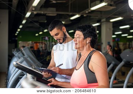 Young male personal trainer with female middle aged client in modern gym. Brunette woman working out on treadmill with the assistance of coach. Healthy lifestyle concept. Selective focus