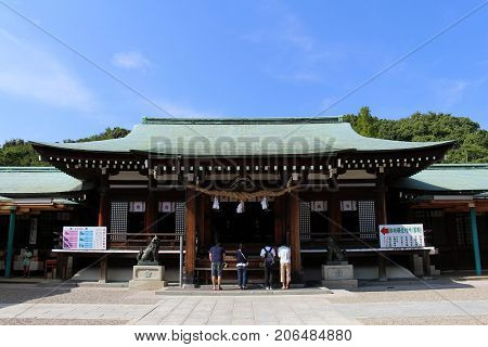 People Praying In Front Of Wooden Japanese Temple In Yamaguchi. Translation: