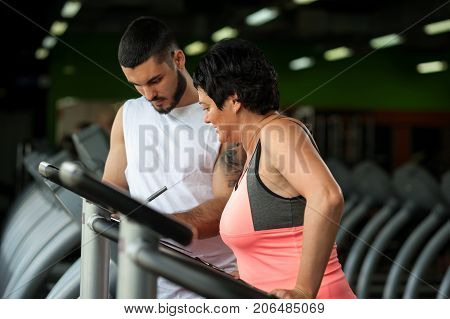 Middle aged brunette woman working out in gym with personal coach. Trainer and his female client discussing nutrition ar training plan together. Healthy lifestyle concept. Selective focus.