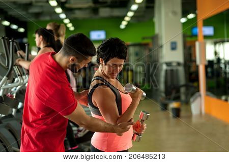 Fitness coach assisting his female client ingym. Middle aged brunette woman working out with weights in modern fitness center. Healthy lifestyle, fitness and sports concept. Selective focus