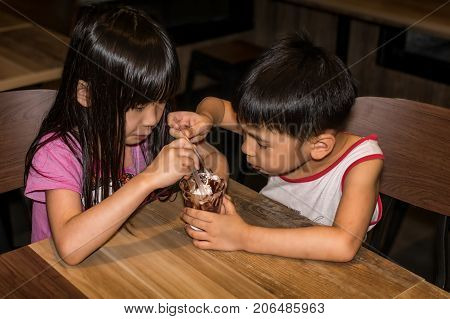 Still Capture of the Moment where Two Child Share a Cup of Chocolate Sundae