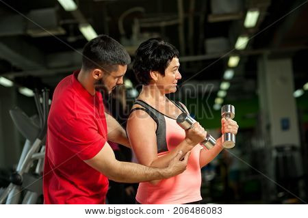 Middle aged caucasian woman doing weight exercise with personal coach. Female brunette working out with assistance of trainer. Healthy lifestyle, fitness and sports concept.
