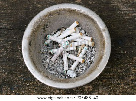 Ashtray at the smoking place in parking full of the variety of cigarettes after smoked