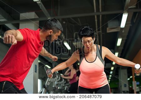 Middle aged female client working out with dumbbells. Young male fitness coach assisting brunette woman in gym. Healthy lifestyle concept.