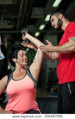 Middle aged woman doing triceps exercise with assistance of personal coach. Male trainer working with brunette woman. Healthy lifestyle, fitness and sports concept.
