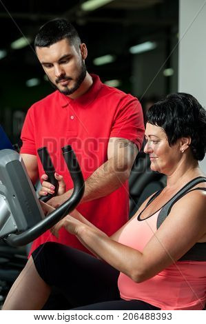 Young personal coach working with middle aged female client in gym. Brunette woman exercising on machine. Healthy lifestyle, fitness and sports concept.