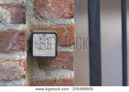 small door access controller on a red brick wall