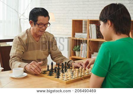 Cheerful Vietnamese senior man and caregiver playing chess